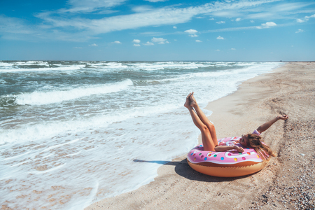 Photo for Girl relaxing on donut lilo on the beach. Playing with inflatable ring. Summer holiday idyllic on a tropical island. - Royalty Free Image