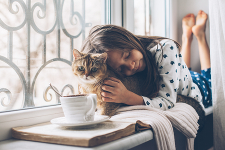 Photo for Child in pajamas relaxing on a window sill with pet. Lazy weekend with cat at home. Cozy scene, hygge concept. - Royalty Free Image