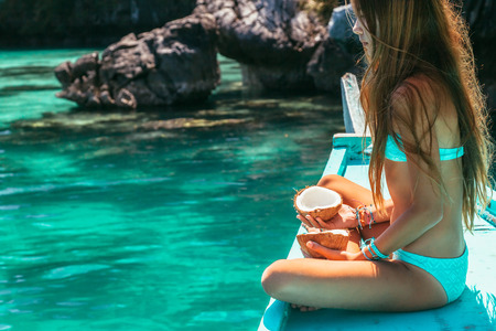 Foto de Young girl relaxing on the boat, looking at clear sea water and eating coconut. Travelling tour in Asia: El Nido, Palawan, Philippines. - Imagen libre de derechos