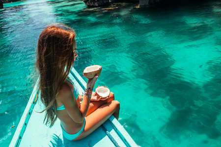 Foto de Young girl relaxing on the boat and eating coconut over clear sea water. Travelling tour in Asia: El Nido, Palawan, Philippines. - Imagen libre de derechos