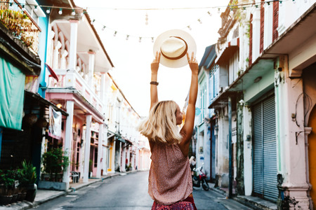 Photo pour Boho girl walking on the city street. Travelling in Phuket Old Town in Thailand. - image libre de droit