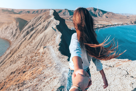 Photo pour Girl walking on the mountain top over blue sea view. Follow me - POV. - image libre de droit