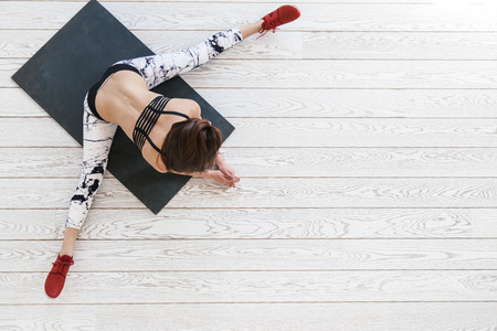 Photo for Young beautiful girl wearing fashion sports wear doing pilates exercise on black mat on white wooden floor in bright gym, top view overhead - Royalty Free Image
