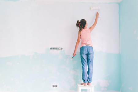 Foto de Preteen child painting the wall in her room in blue and white colors. Young girl making interior renovation at home. - Imagen libre de derechos