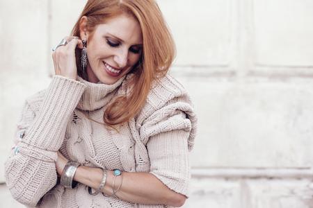 Foto de Boho jewelry on model: ethnic rings, bracelets and earrings. Beautiful woman wearing warm woolen sweater and fashion jewellery. Street photo in pastel tone. - Imagen libre de derechos