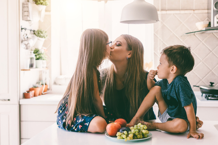 Foto de Mom with her two children sitting on the kitchen table and eating fruits together. Mother with daughter and toddler son having breakfast at home. Happy lifestyle family moments. - Imagen libre de derechos