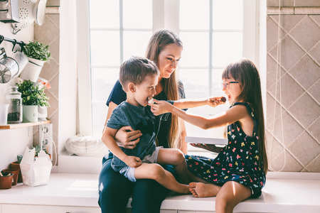 Photo for Mom with her two children sitting on the kitchen table and eating candies. Mother with daughter and toddler son having breakfast at home. Happy lifestyle family moments. - Royalty Free Image