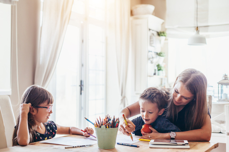 Foto de Mom playing with her 2 years old son and preschool daughter at home. Mother drawing with pencils together with children. - Imagen libre de derechos