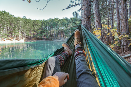 Foto de Woman relaxing in the hammock by the lake in the forest, POV view of legs in trekking boots. Hiking in cold season. Wanderlust concept scene. - Imagen libre de derechos