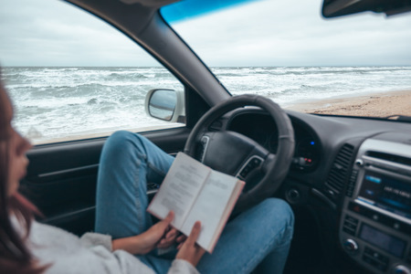 Photo pour Young girl reading in car over sea waves outside. Weekend trip in bad rainy weather. Dramatic winter travel concept. - image libre de droit