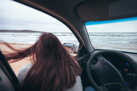 Foto de Young girl relaxing in car and looking at sea waves outside. Weekend trip in bad rainy weather. Dramatic winter travel concept. - Imagen libre de derechos