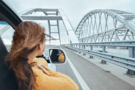 Foto de Rear view of pre teen girl in car looking forward on a bridge at weekend road trip - Imagen libre de derechos