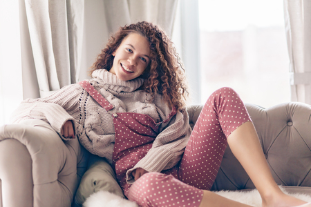 Foto de Hipster teenage girl with curly hair wearing beige knitted sweater and pink polka dot jumpsuit relaxing on a couch indoor - Imagen libre de derechos