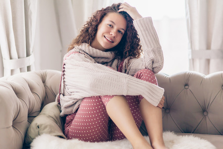 Photo for Hipster teenage girl with curly hair wearing beige knitted sweater and pink polka dot jumpsuit relaxing on a couch indoor - Royalty Free Image