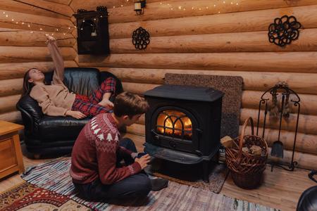 Foto de Teenage friends relaxing by the fireplace inside wooden cabin. Warm and cozy winter holiday indoor concept. - Imagen libre de derechos