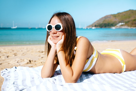 Foto de Teenage girl spending her vacations on the Naiharn beach, Phuket, Thailand. Sunny day, good weather for summer relaxing. - Imagen libre de derechos