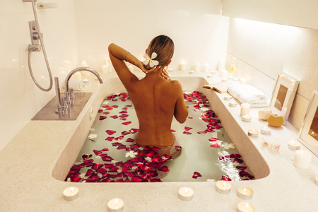Foto de Woman relaxing in luxury bath decorated with candles and flower petals. Organic skin care in tropical spa resort. - Imagen libre de derechos