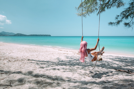 Foto de Back view of girl with pink hear having fun on swing hanging on tree at tropical beach with white sand. Luxury vacation on paradise island. - Imagen libre de derechos