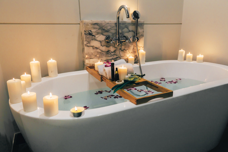 Foto de Prepared luxury spa bath decorated with flowers and candles, with wooden tray on it - Imagen libre de derechos