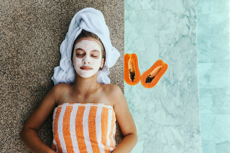 Photo for Lifestyle image of 12-14 years old teen applying organic fruit facial mask with papaya. Top view photo of teenage girl wrapped in towel doing anti blemish face treatment by the pool side. - Royalty Free Image