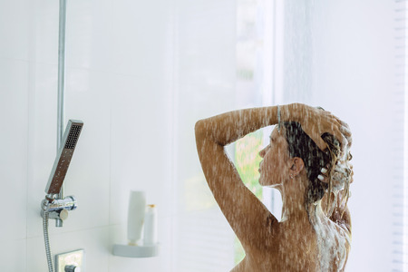 Photo pour Back view of woman taking shower in modern white bathroom in the morning. Daily routine lifestyle photo. - image libre de droit