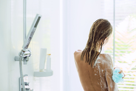 Foto de Back view of woman taking shower in modern white bathroom in the morning. Daily routine lifestyle photo. - Imagen libre de derechos