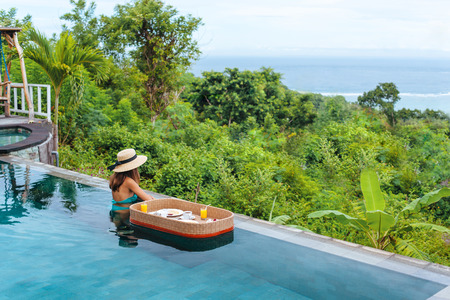 Photo for Girl relaxing and eating in luxury infinity pool with a view. Served floating breakfast in tropical Bali resort. - Royalty Free Image