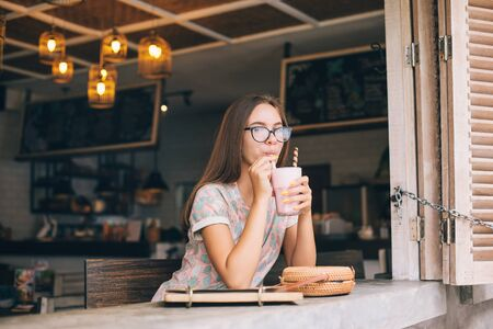 Photo pour Positive teen girl enjoying sweet smoothie while spending time in loft cafe - image libre de droit