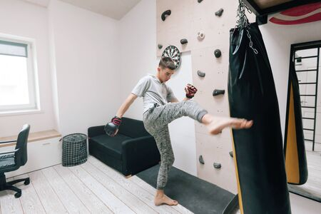 Foto de 16-17 years old teenage boy workout with boxing bag in home gym room. Young teen male having hobby to be strong and sportish man. - Imagen libre de derechos
