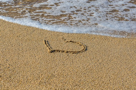 Photo pour Heart drawn on wet sand beach. Part of the heart is washed away by a wave. Symbol of the beginning or the end of romantic love. Summer vacation concept. Romantic background with space for text - image libre de droit