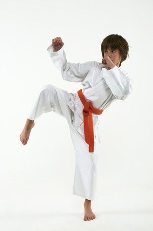 boy practicing karate on white background