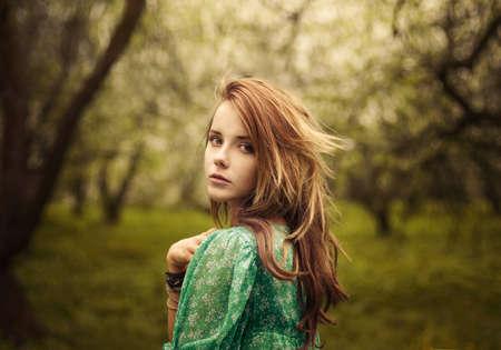 beautiful girl looks in the garden