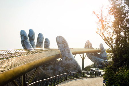 Photo pour Golden Bridge in hands Da Nang, Vietnam - Ba Na Hills Park. The new symbol of Vietnam. Bright Sunrise at the bridge. Colorful horizontal image of Bana Hills Bridge. Ideal for travel agencies, advertising, banners, web etc - image libre de droit