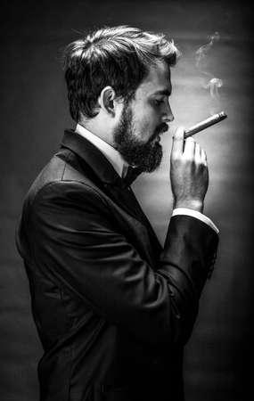 Photo pour black and white portrait of bearded smoking cigar gentleman in a suit - image libre de droit