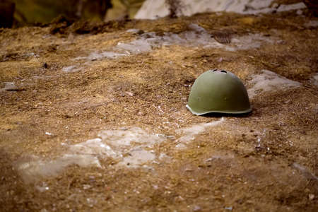 Foto de damaged helmet on the battlefield, background image - Imagen libre de derechos