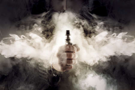 Photo for electronic cigarette in hand in the middle of thick smoke, background image - Royalty Free Image