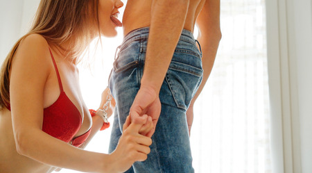 Photo pour Passionate couple having sex on bed - Sensual woman tied up with handcuffs seducing her man - Sexy and erotic moments of lovers - Sexual and love concept - image libre de droit