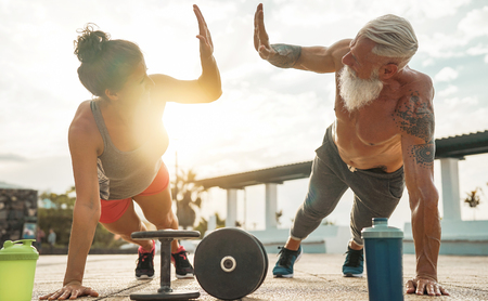 Foto de Fitness couple doing push ups exercise at sunset outdoor - Happy athletes making gym workout session outside - Concept of people training, fit, empowering and bodybuilding lifestyle - Imagen libre de derechos