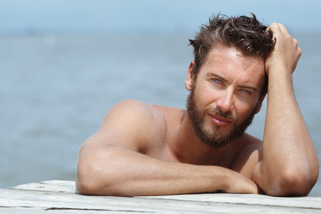 Foto de Close up Portrait of Smiling Gorgeous Handsome Man with No Shirt Posing at the Sea - Imagen libre de derechos