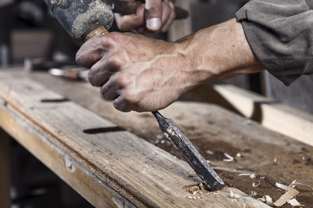 Photo pour Hands of carpenter with chisel in the hands on the workbench in carpentry - image libre de droit