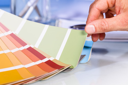 Foto de Close up of Artist hand browsing color samples in palette in studio background - Imagen libre de derechos