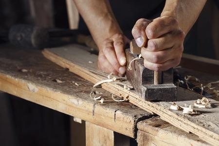 Photo pour Close up of a carpenter planing a plank of wood with a hand plane - image libre de droit