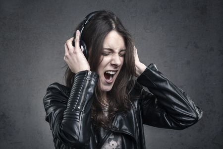 Photo for young Woman with head phones listening to music and Singing against dark wall background; - Royalty Free Image