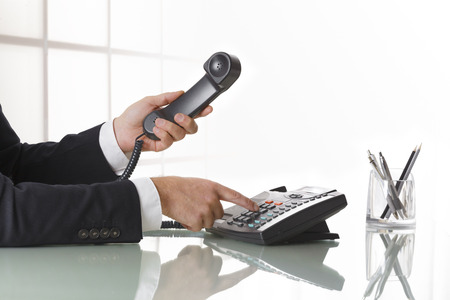 Photo pour Businessman with dark gray suit dialing the number on a black landline telephone.  Closeup of his hand and the telephone on an office table whit pen. Concept of business and communication. - image libre de droit