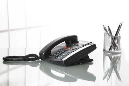 Photo pour Close up of black landline phone on an office desk with white background - image libre de droit