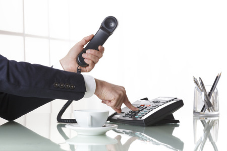 Photo pour Hand of a businessman with dark gray suit holding the receiver of a black landline telephone while firmly pressing a button on telephone, with a cup of coffee and pens on a white office table. Concept of business and communcation. - image libre de droit