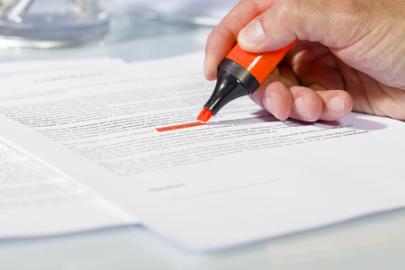 Photo pour Close-up of man hand with highlighter over document, checking the content before signing. Concept of business and agreement - image libre de droit