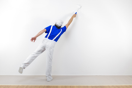 Photo for Rear view of painter in white workwear, blue t-shirt and cap with paintroller painting a white wall. - Royalty Free Image