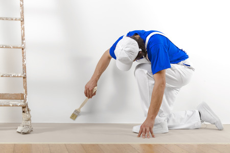 Photo for Painter man at work with brush painting a white wall. - Royalty Free Image