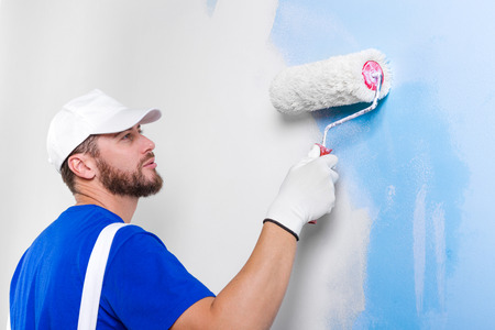 Photo for Portrait of handsome young painter in white dungarees, blue t-shirt, cap and gloves painting a wall with paint roller. - Royalty Free Image